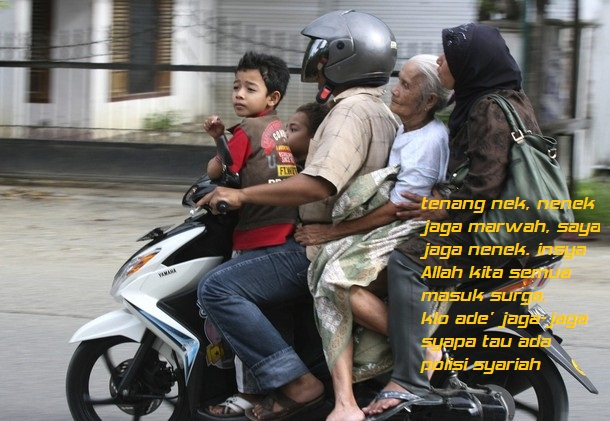 A man evacuates his family members in a motorcycle in Banda Aceh after a strong earthquake struck Indonesia province
